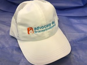 White hat featuring the orange unlocking symbol with the text: Advocacy Day for Access & Independence